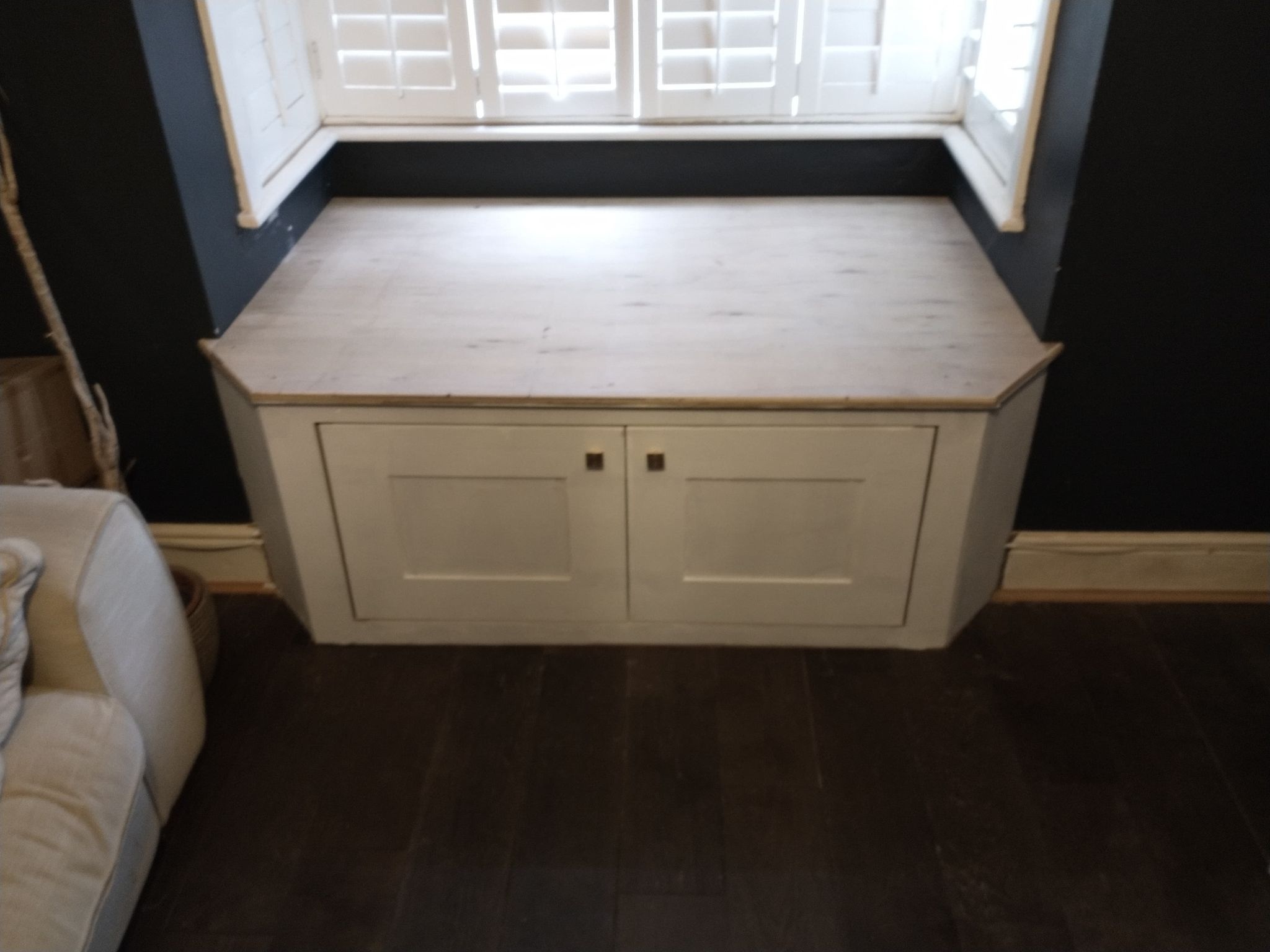 Large window seat with storage cupboards.